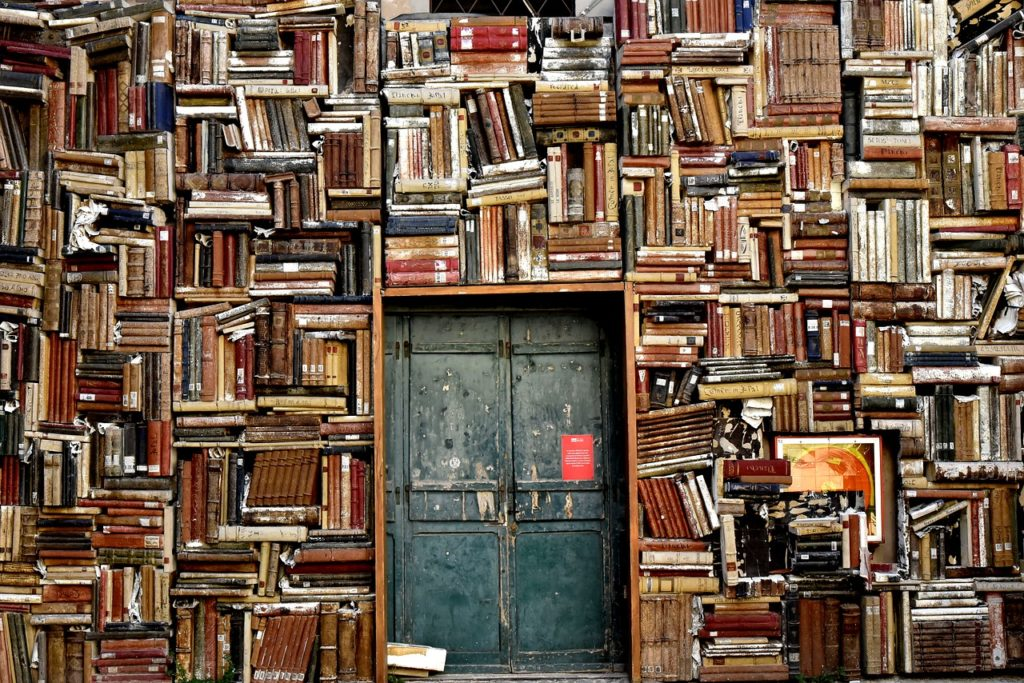 Eine Wand voller Bücher mit einer Tür