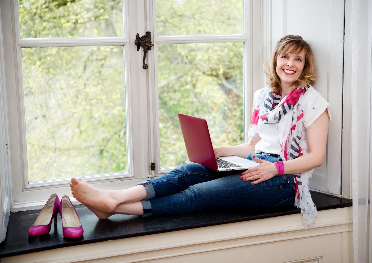 Alex Broll mit einem Laptop am Fenster - aktive Pausen, Bewegung und Selbstwert