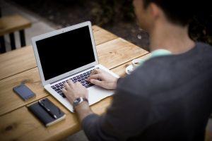 Ein Mann schreibt an einem Laptop