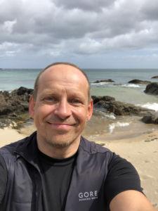 Strahlender Tom Oberbichler mit Meer im Hintergrund - Regeneration