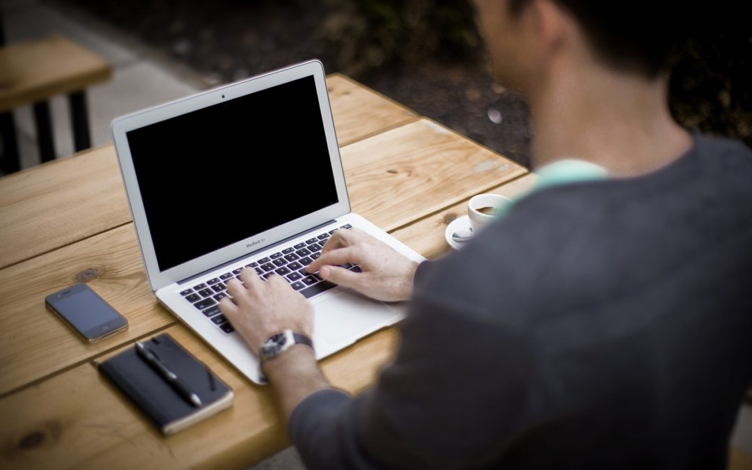 Schriftsteller am Laptop beim Sachbuch schreiben